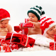 Three babies in xmas costumes playing with gifts — Stock Photo #8084109