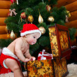 Cute baby boy looking into case with gifts — Stock Photo #8084435