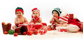 Four babies in xmas costumes playing among gifts — Stock Photo