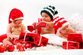 Three babies in xmas costumes playing with gifts — Stock Photo