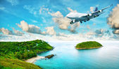 Jet plane over the tropical island — Stock Photo