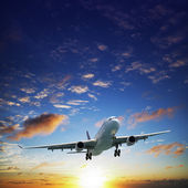Jet airplane in a sky at sunset time — Stock Photo