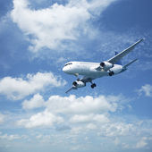 Jet plane in a blue cloudy sky — Stock Photo