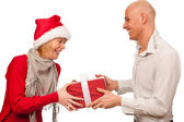 Christmas gift - Girl in santa dress giving a gift to a man — Stock Photo