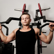 Man doing fitness training on machine with weights in a gym — Stock Photo #8326053