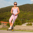 Cute teenage girl in pink dress on scooter — Stock Photo #8326695