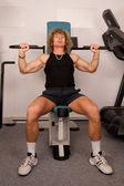 Man doing fitness training on machine with weights in a gym — Stock Photo