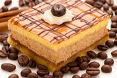 Coffe cake on a plate decorated with cinnamon and coffee beans — Stock Photo