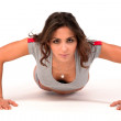 Attractive young woman doing pushups over white background — Stock Photo #8878349