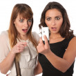 Two attractive young women checking a short message — Stock Photo