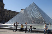Glass Pyramid and tourists at the Louvre Museum — Stock Photo