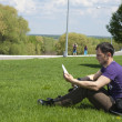 Young man reading in the park — Stock Photo
