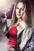 Fashion portrait of sexy woman with gun — Stock fotografie