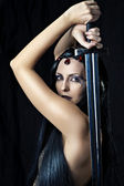 Young sexy woman warrior holding sword — Stock Photo