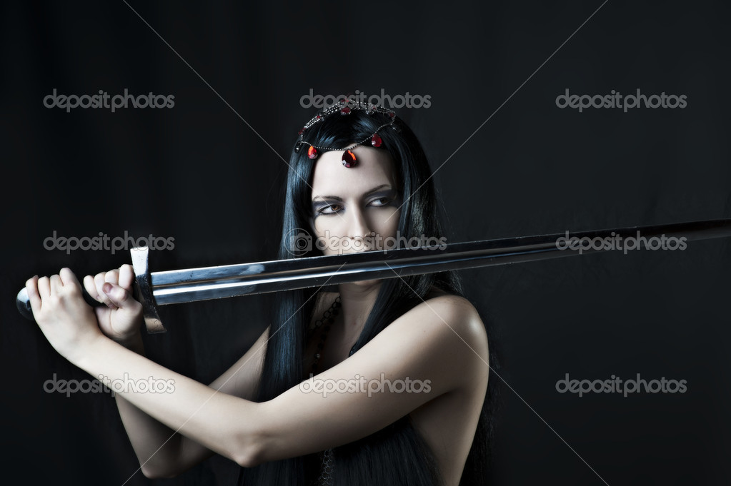 Fashion portrait of young sexy brunette woman with sword on black background — Stock Photo #8818170