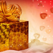 Royalty-Free Stock Photo: Golden  gift with ribbon and hearts.