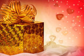 Golden gift with ribbon and hearts. — Stock Photo