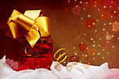 Red gift with golden ribbon with hearts. — Stock Photo