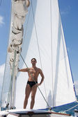 Sexy young man sailing on white yacht — Stock Photo