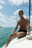 Handsome young adult man sailing on yacht — Stock Photo