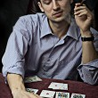 Young man with cigar playing poker. - Stock Photo