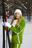 Woman skier in snowy forest with ski poles — Stock Photo