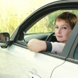 Stock Photo: Beautiful young woman in car looking from window on nature backg