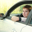 Beautiful young woman in car looking from window on nature backg — Stock Photo