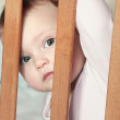 Adorable funny baby boy looking out the wooden bed with big eyes — Stock Photo