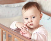Funny small baby girl holding finger near the nose on face stand — Stock Photo