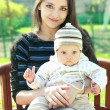 Beautiful young mother holding baby on hand sitting on bench on — Stock Photo #10387725