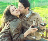Happy couple drinking red wine outdoor. Young man kissing laughi — Stock Photo