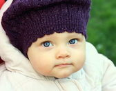 Beautiful funny baby in hat with big blue eyes on nature green b — Stock Photo