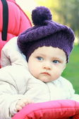 Funny baby girl in hat outdoor sit in stroller and looking. Clos — Stock Photo