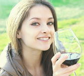 Beautiful young woman drinking wine on nature green background — Stock Photo