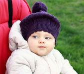 Bebê engraçado no chapéu sentado ao ar livre em vermelho brilhante carrinho na gree — Fotografia Stock