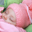 Royalty-Free Stock Photo: Sleeping beautiful newborn baby girl in pink hat outdoor