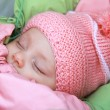 Sleeping beautiful newborn baby girl in pink hat outdoor — Stock Photo #8205534