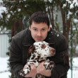 Happy young man holding Dalmatian dog on the hands - Stock Photo