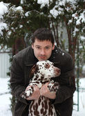 Happy young man holding Dalmatian dog on the hands — Stock Photo