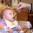 Mother feeding little baby girl from the spoon in the kitchen in — Stock Photo #8416658