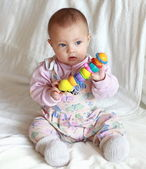 Beautiful baby girl sitting and holding in the hands colorful br — Stock Photo