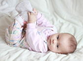 Beautiful small baby girl lying on the back and holding feet her — Stock Photo