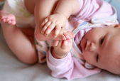 Closeup portrait of beautiful baby girl holding foot herself and — Stock Photo
