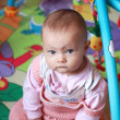 Adorable baby girl sitting and playing in developmental mat — Stock Photo #8644148