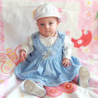 Adorable baby girl sitting in beautiful blue dress and funny hat — Stock Photo
