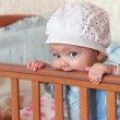 Funny baby girl in hat standing and biting the bed and looking — Stock Photo