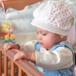 Adorable baby girl standing in bed in beautiful cap in bedroom — Stock Photo