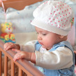 Adorable baby girl standing in bed in beautiful cap in bedroom — Stock Photo #8940033