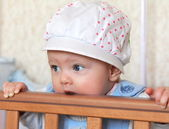 Closeup portrait of funny baby girl in hat standing and biting t — Stock Photo